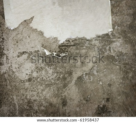 Grunge Background. Aged wall with a scrap of paper