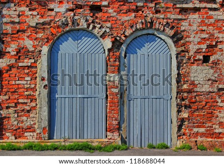 Grunge background of two arch wooden doors and red ancient bricklaying of the 18th eyelid.