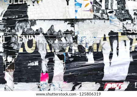 Grunge background on billboard with old torn posters / Torn street poster /