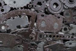 Grunge Background Rusty metal parts. Gears, fittings, wires, tubes other old products are welded to uneven iron sheets. Perfect for background and grunge design.