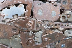 Grunge Background Rusty metal parts. Gears, fittings, wires, tubes other old products are welded to uneven iron sheets.