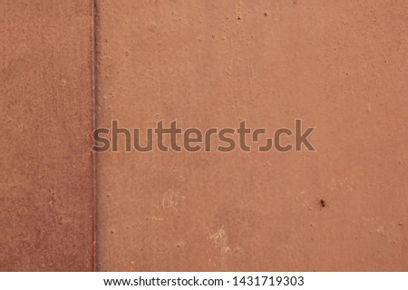 Grunge background texture. An old metal wall painted with  light red paint, with a rough surface.  There is insect on the right down. On the left is direct vertical line of joint dividing the image. #1431719303