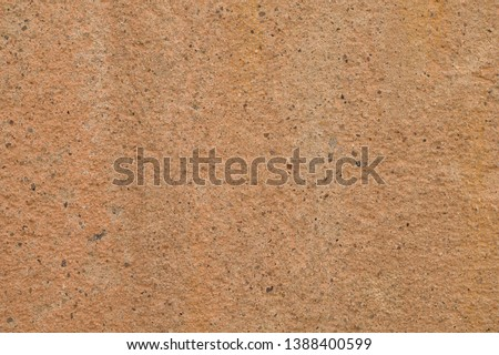 Grunge background texture. Light brown background with a light pink tint. The surface of the old concrete wall. Over the entire surface of the wall there are many inclusions of small granite pebbles.  #1388400599