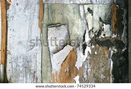 Grunge background / texture on a dirty wall with pieces of paper
