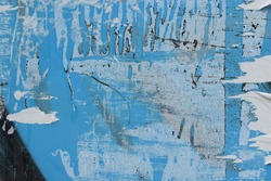 Grunge background texture with torn paper stains and scratches on glass surface. City wall abstract detail.