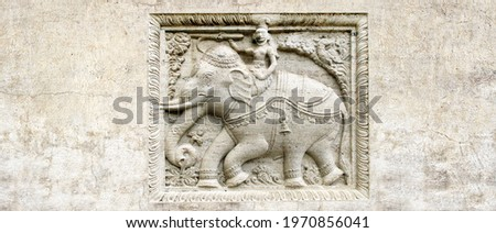 Grunge background with stone texture and bas-relief with elephant rider. Horizontal banner with ancient ornament. Copy space for text. Mock up template Stockfoto ©