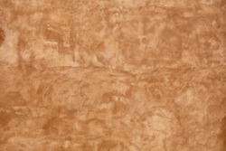 Grunge beige brown faded uneven old aged daub plaster wall texture background with stains and paint strokes, close up