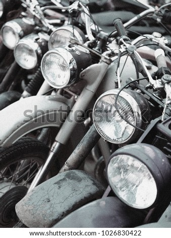 Grunge black and white photography of group motorbikes parked together. Retro motorbikes background. Classic vintage motorcycles. Vintage effect with noise and grain