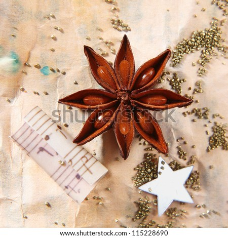 Grunge Christmas still life with star anise spice, a traditional star and music notes on stained, aged, crumpled vintage paper with scattered seeds