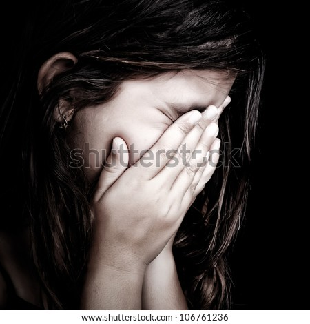Grunge close-up portrait of a girl crying and covering her face isolated on black
