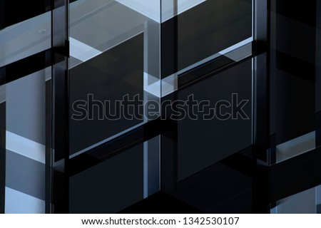 Grunge double exposure photo of windows in darkness. Structural glazing of an office building. Abstract modern architecture background. Glass wall with angular pattern of steel or aluminum framework.  #1342530107