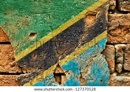 Grunge flag of Tanzania on old wall background.