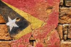 Grunge flag of Timor on old wall background.
