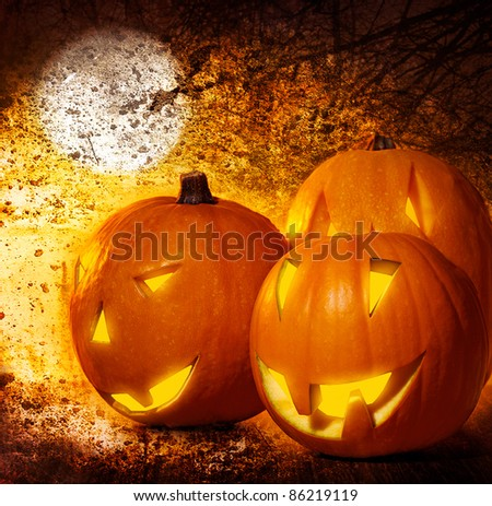 Grunge Halloween background, pumpkins on the cemetery at night, scary spooky decoration, autumn holiday