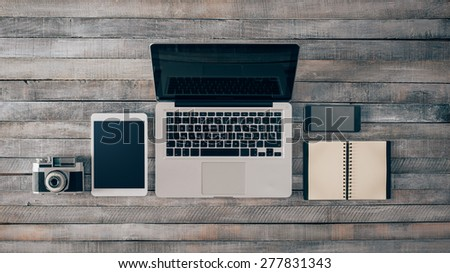 Grunge hipster wooden desktop with computer, digital tablet, vintage camera, smart phone and notebook, top view