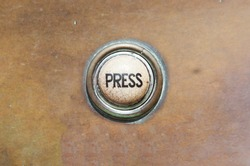 Grunge image of a button from the control area for an old elevator lift or doorbell