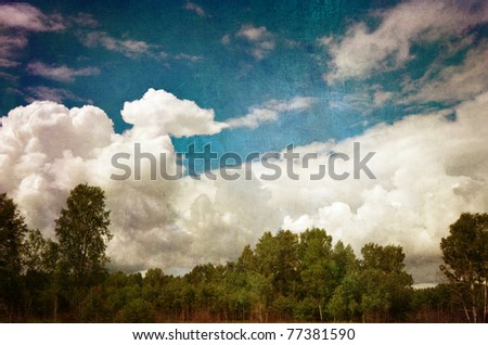 grunge image of a green woods against blue cloudy sky