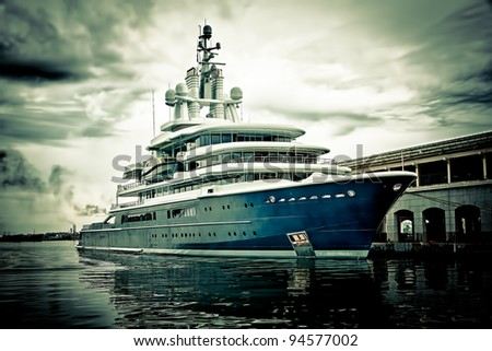 Grunge image of a modern scientific research or tourism ship docked in a pier with a violent storm approaching stock photo