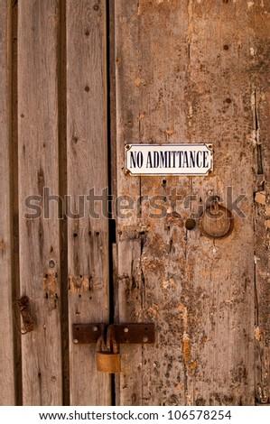 Grunge No Admittance sign on old wooden door locked with padlock in Mdina, Malta
