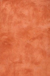 Grunge orange brown faded uneven old aged daub plaster wall texture background with stains and paint strokes, close up