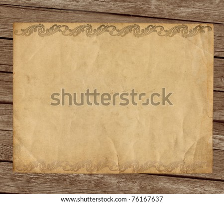 Grunge paper with ornament on wooden background
