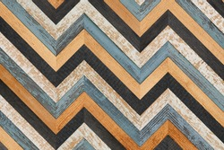 Grunge parquet floor. Colorful wooden wall with chevron pattern made of thin slats. Old weathered wooden planks texture.