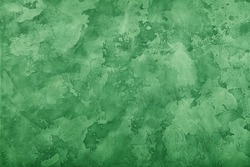 Grunge pastel green faded uneven old aged daub plaster wall texture background with stains and paint strokes, close up