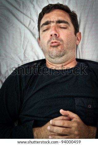 Grunge portrait of a sick hispanic man laying in bed and coughing