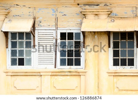 Grunge ramshackle windows with broken glass on yellow wall