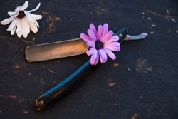 Grunge razor with flowers on the old black background
