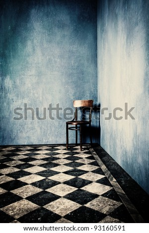 grunge room with blue old walls tiled floor and wooden chair in corner - stock photo