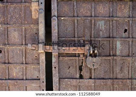 grunge rusty forged gates with padlock - stock photo