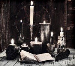 Grunge still life with burning candles and open diary book on witch table.  Esoteric, gothic and occult background, Halloween mystic concept.