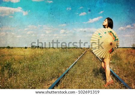 Grunge style umbrella girl on railroad trucks - stock photo