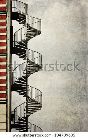 grunge textured picture of a spiral staircase at the edge of an house