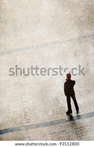 grunge textured picture with a businessman figurine standing upon a financial sector of a newspaper