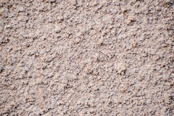 Grunge textured wall pattern. Brown detailed surface. Exterior of a building closeup. Abstract surface. Selective focus on the bumps, blurred background.