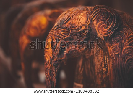 Grunge vintage style photo of a little wooden elephants with artistically carved drawings, traditional asian and african souvenir