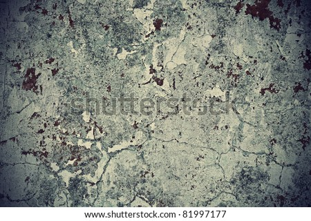 Grunge wall texture background. Paint cracking off dark wall with rust underneath.
