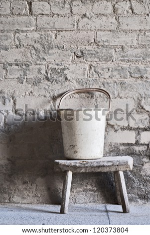 grunge wall, white plastic bucket on the wooden seat background at the mill warehouse
