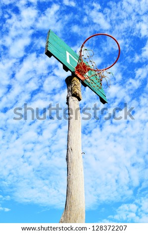 Grunge wooden basket hoop isolated on a blue sky background.