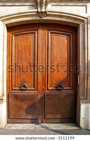Grunge wooden door with bronze handles in Paris