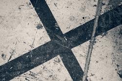 Grungy dark stylised black cross on a flat damaged surface.