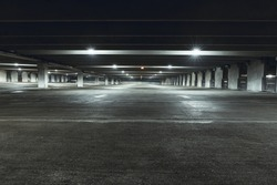Grungy, dimly lit empty parking garage with overhead lights and an exit sign hanging from the ceiling.