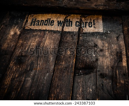 Grungy Filtered Handle WIth Care Sign On An Old Wooden Shipping Crate