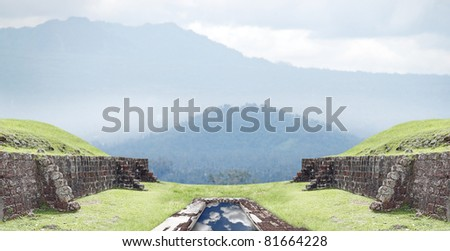 Grungy masonry brick wall guarding a water fountain with a reflection of the cloudy blue sky on top of a green grassy hill overlooking a beautiful tropical scenery of a mountain range.