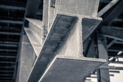 grungy monochrome style image of h beam or i beam iron metal structure frame under bridge base pole of highway construction site, close up shot low key dark tone image
