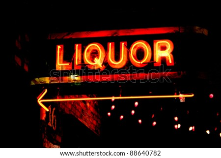 grungy neon sign pointing the way to a bar