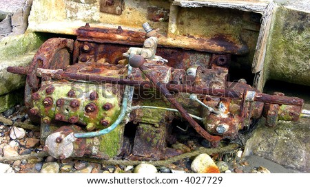 Grungy old auto engine rusting away on the beach