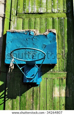Grungy old damaged blue basketball hoop on a green gate with peeling painting